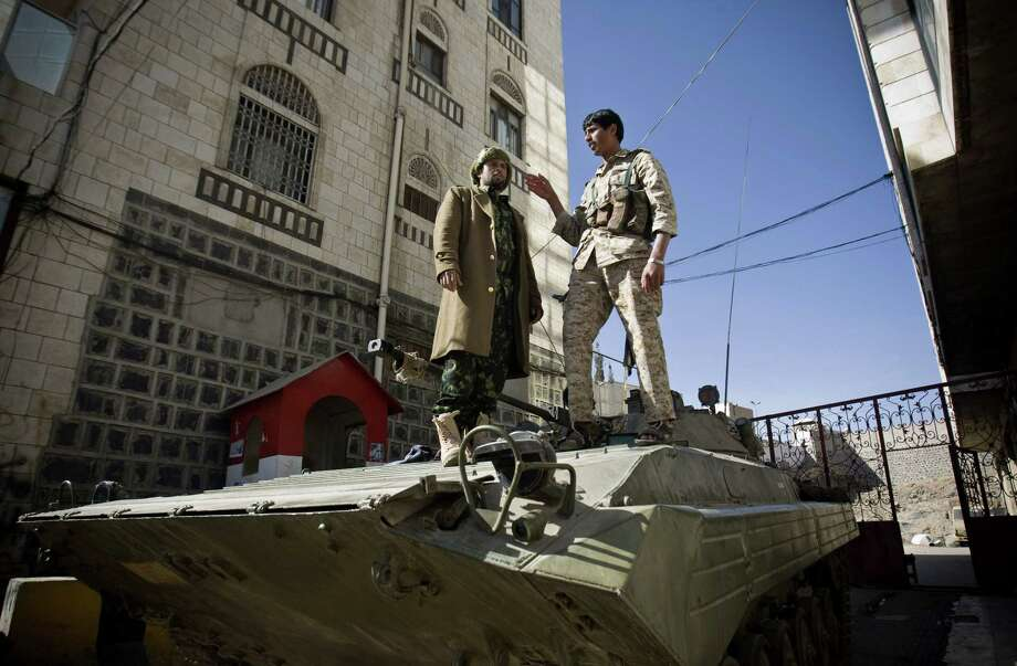 Houthi Shiite Yemeni wearing army uniforms stand atop an armored vehicle, which was seized from the army during recent clashes, outside the house of Yemen's President Abed Rabbo Mansour Hadi in Sanaa, Yemen, Thursday, Jan. 22, 2015. Heavily armed Shiite rebels remain stationed outside the Yemeni president's house and the palace in Sanaa, despite a deal calling for their immediate withdrawal to end a violent standoff. (AP Photo/Hani Mohammed) Photo: AP / AP