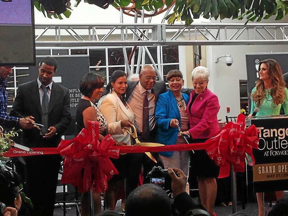 Nancy Wyman, right, wields a scissors with Foxwoods officials as Sonia Baghdady,far  right, looks on. Photo: Joe Amarane/Register