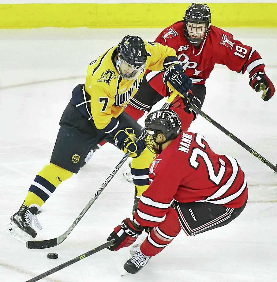 Quinnipiac's Sam Anas, left, carries the puck past a pair of RPI defenders during Thursday's game. Photo: Catherine Avalone — Register  / New Haven RegisterThe Middletown Press