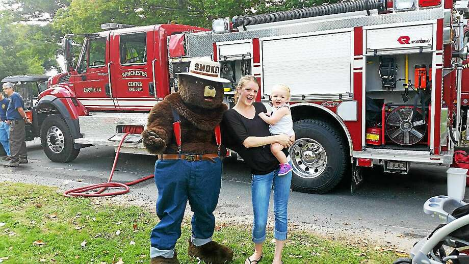Forest fire prevention character Smokey Bear (aka Sarah Howard of the Winchester Volunteer Fire Department) joined Lauren Howard and daughter Jiana, 1, at Winchester Center Day on the Winchester Town Green at Newfield Road and Route 263 in Winchester Saturday afternoon. Photo: NF Ambery — The Register Citizen