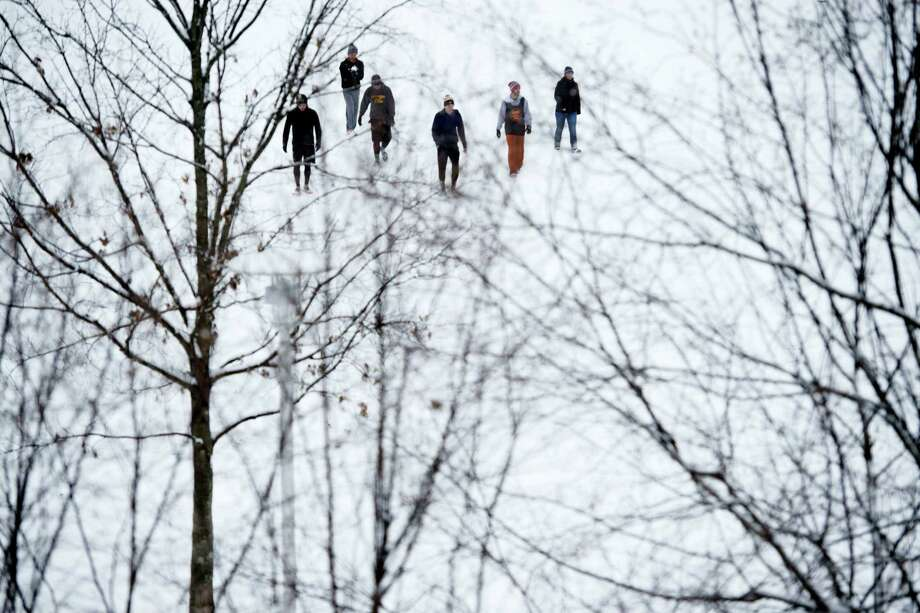 A group of friends enjoy the snow at a park in Knoxville, Tenn., on Wednesday, Jan. 20, 2016. As people in the South and East readied themselves for a nor'easter that might bring heavy snowfall by week's end, snow fell on much of Kentucky and Tennessee and contributed to at least one traffic-related death Wednesday. Photo: Saul Young/Knoxville News Sentinel Via AP   / Knoxville News Sentinel
