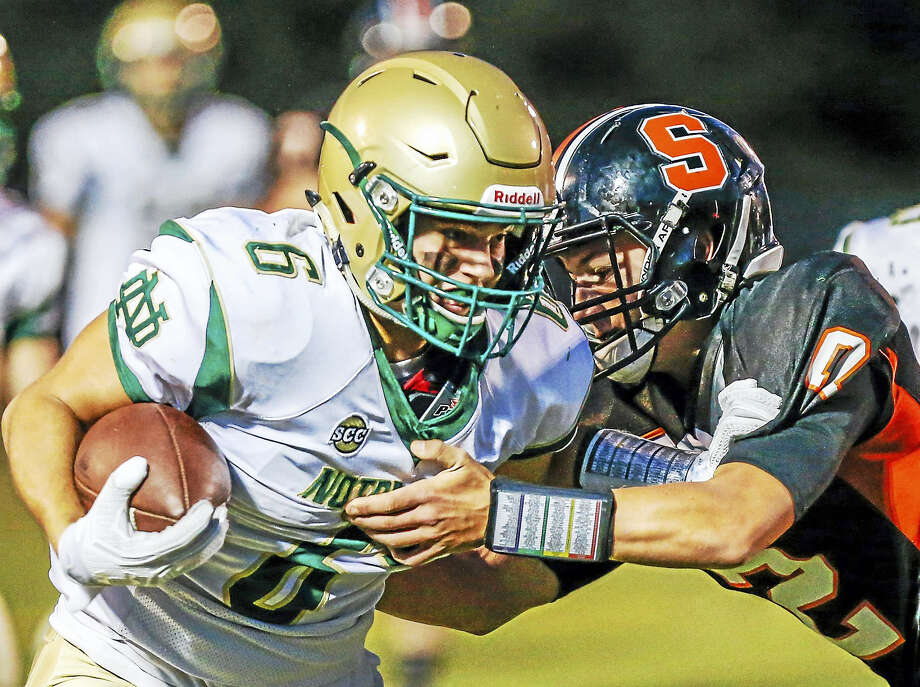 Notre Dame's Joshua Witkowsky eludes the tackle attempt of Shelton's David Wells during Friday evenings football action in Shelton.-John Vanacore/New haven Register Photo: Journal Register Co. / John Vanacore/New Haven Register`