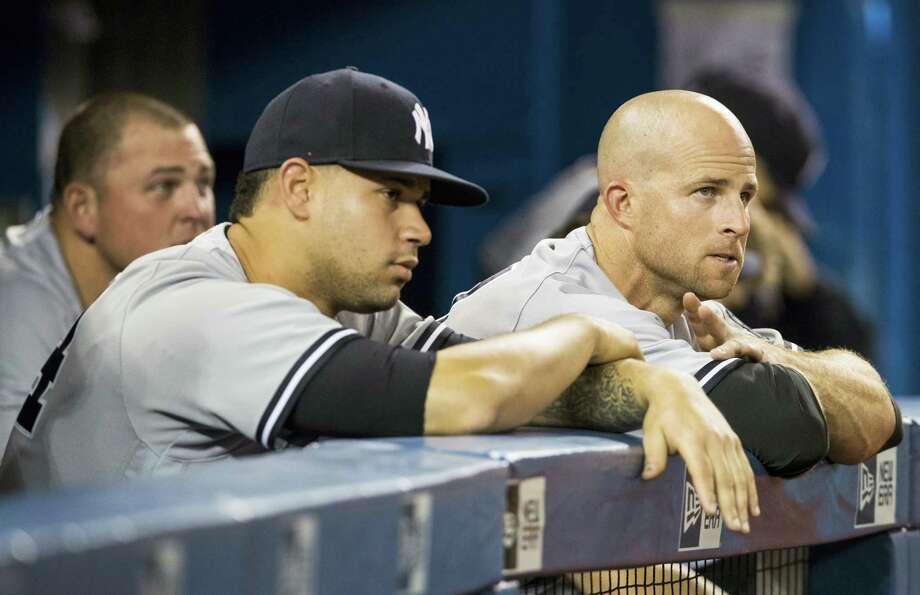 Brett Gardner, right, and Gary Sanchez, front left, watch the last few outs of Friday's game. Photo: Mark Blinch — The Canadian Press Via AP  / The Canadian Press
