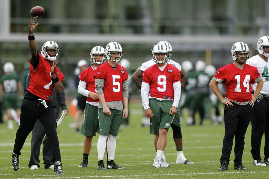 New York Jets quarterback Geno Smith (7) throws as quarterbacks Matt Simms (5), Bryce Petty (9) and Ryan Fitzpatrick (14) look on during OTAs on Wednesday in Florham Park, N.J. Photo: Julio Cortez — The Associated Press  / AP