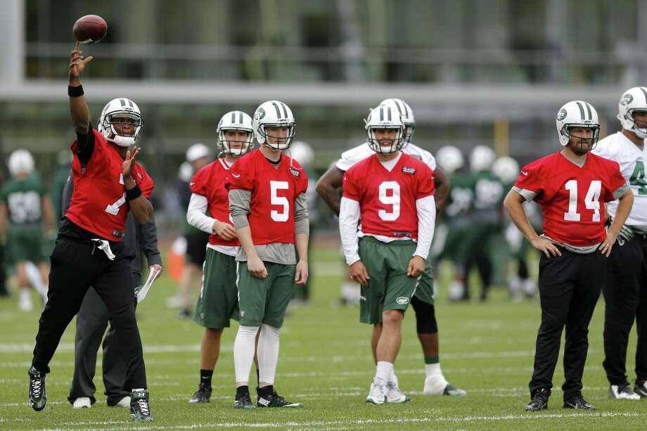 New York Jets quarterback Geno Smith (7) throws as quarterbacks Matt Simms (5), Bryce Petty (9) and Ryan Fitzpatrick (14) look on during OTAs on Wednesday in Florham Park, N.J. Photo: Julio Cortez — The Associated Press  / AP