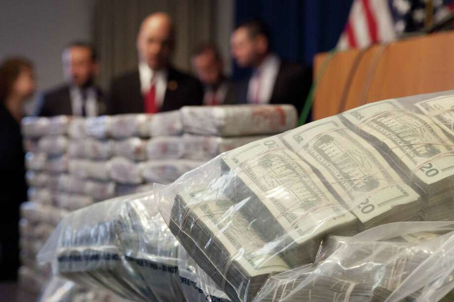 Sacks of money, right, worth $2 million, and 154 pounds of heroin, left, worth at least $50 million, are displayed at a Drug Enforcement Administration news conference, Tuesday, May 19, 2015 in New York. The DEA called the heroin seizure its largest ever in New York state. Officials said on Tuesday that most of the drugs were found in an SUV in the Bronx following a wiretap investigation. (AP Photo/Mark Lennihan) Photo: AP / AP
