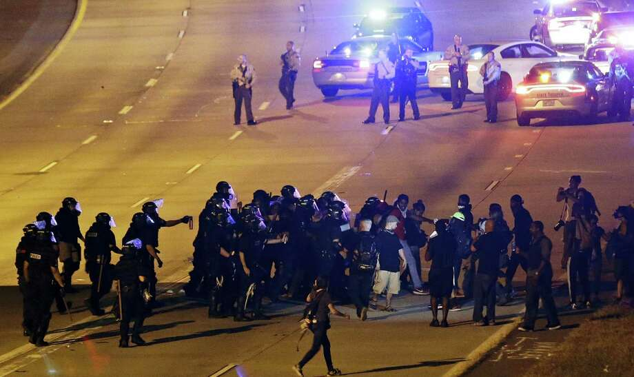 Police confront protesters blocking I-277 during a third night of unrest following Tuesday's police shooting of Keith Lamont Scott in Charlotte, N.C., Thursday, Sept. 22, 2016. (AP Photo/Gerry Broome) Photo: AP / Copyright 2016 The Associated Press. All rights reserved.