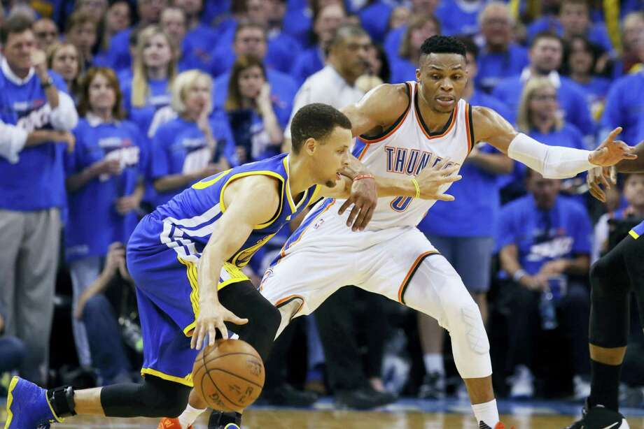 Warriors guard Stephen Curry, left, tries to drive around the Thunder's Russell Westbrook during the second half on Sunday. Photo: Sue Ogrocki — The Associated Press  / AP2016