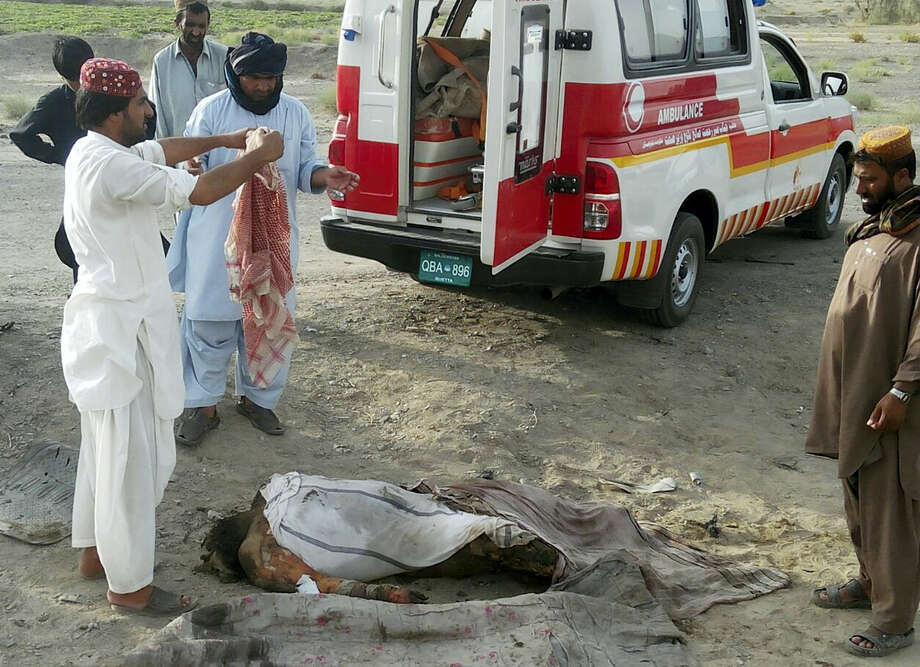 This photo taken by freelance photographer Abdul Malik on May 21, 2016 purports to show volunteers standing next to a dead body by the destroyed vehicle, in which Mullah Mohammad Akhtar Mansour was allegedly traveling in the Ahmed Wal area in Baluchistan province of Pakistan, near Afghanistan border. Photo: AP Photo/Abdul Malik  / Copyright 2016 The Associated Press. All rights reserved. This material may not be published, broadcast, rewritten or redistribu