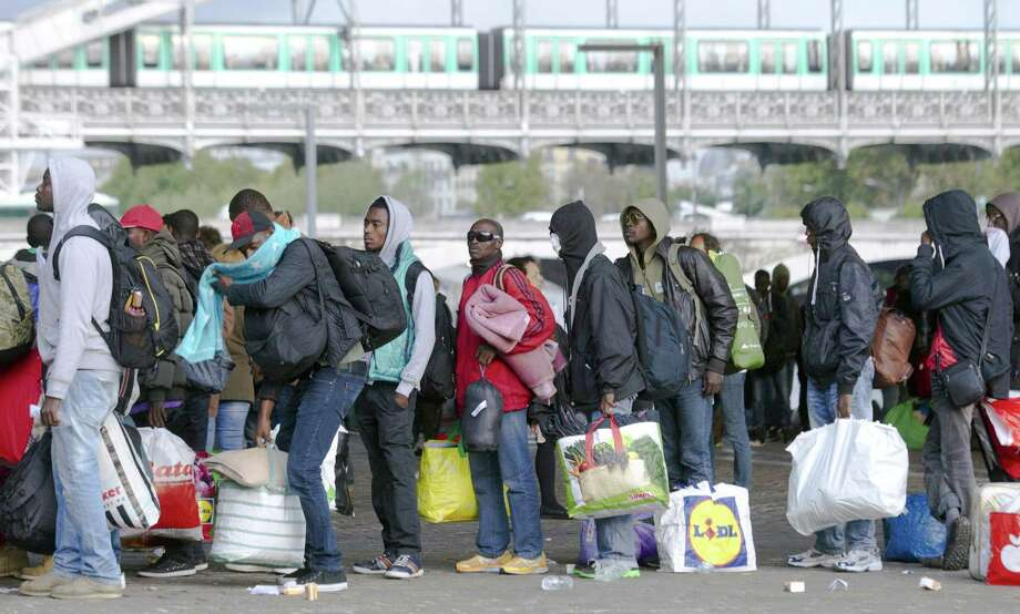 Migrants carrying belongings line up as they leave their tent camp in Paris, France, Thursday. Paris authorities are evacuating more than 500 Syrian and other migrants from tent camps and moving them to special housing as the country steps up efforts to deal with Europe's migrant wave. Photo: Jacques Brinon — The Associated Press  / AP