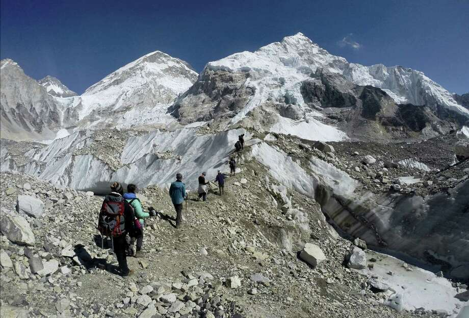 In this Feb. 22, 2016 photo, international trekkers pass through a glacier at the Mount Everest base camp, Nepal. A Nepal official says some 30 climbers have gotten frostbite or become sick on Mount Everest, in addition to two who died in recent days on the world's highest mountain. Photo: AP Photo/Tashi Sherpa, File  / Copyright 2016 The Associated Press. All rights reserved. This material may not be published, broadcast, rewritten or redistribu