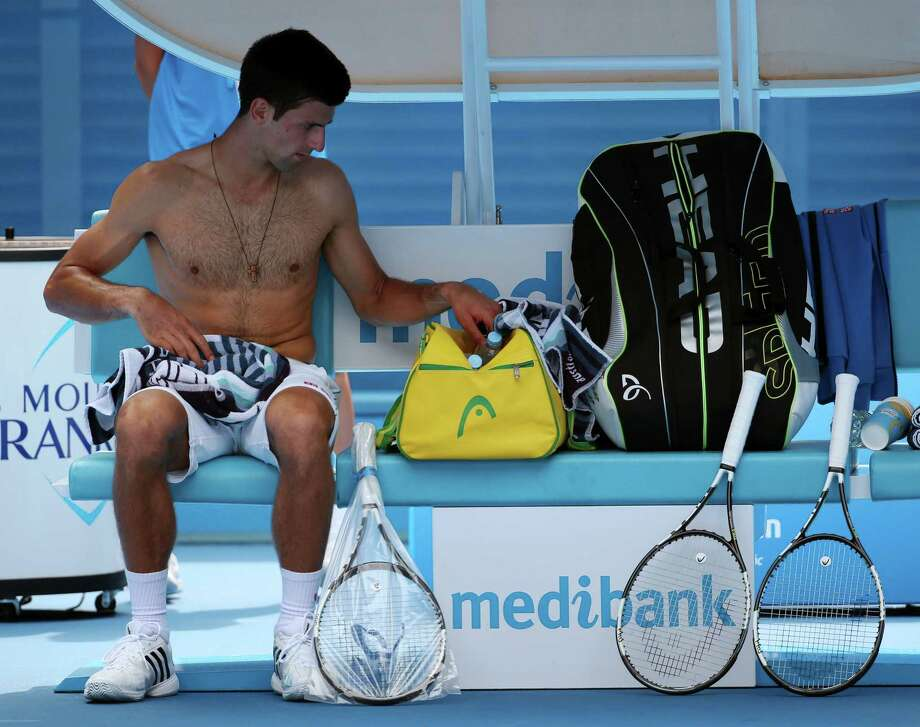 Novak Djokovic rests during a break from his win over Aljaz Bedene in the first round of the Australian Open on Tuesday in Melbourne, Australia. Photo: Rob Griffith — The Associated Press  / AP