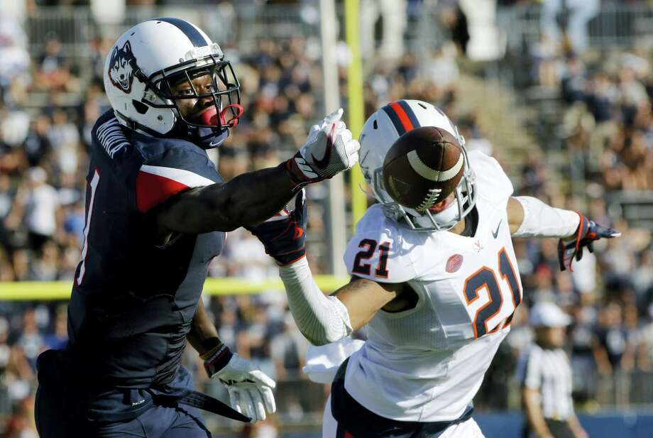 Connecticut's Hergy Mayala, left, and Virginia's Juan Thornhill reach for an incomplete pass during Saturday's game. Photo: The Associated Press File Photo  / AP