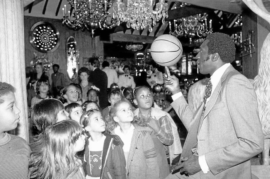 Harlem Globetrotter Meadowlark Lemon balances a basketball on his finger for children attending a children's benefit toy auction at New York's Tavern on the Green on April 23, 1979 in New York. Photo: AP Photo/Dave Pickoff  / AP1979