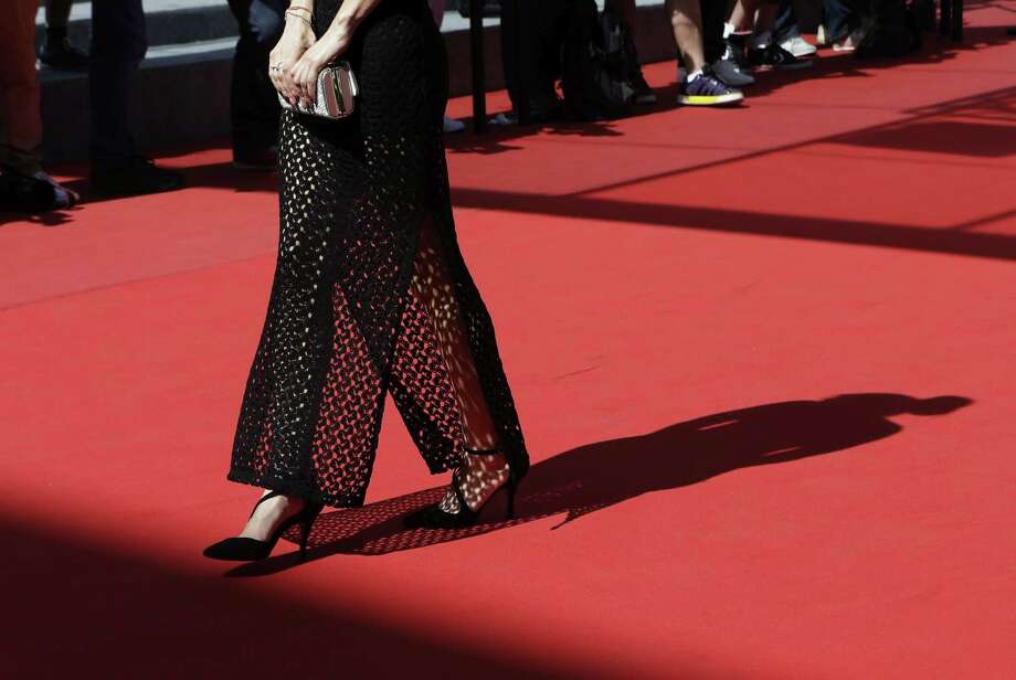 An unidentified guest walks on the red carpet as she arrives for the screening of the film La Loi du Marche (The Measure of a Man) at the 68th international film festival, Cannes, southern France, Monday, May 18, 2015. (AP Photo/Lionel Cironneau) Photo: AP / AP