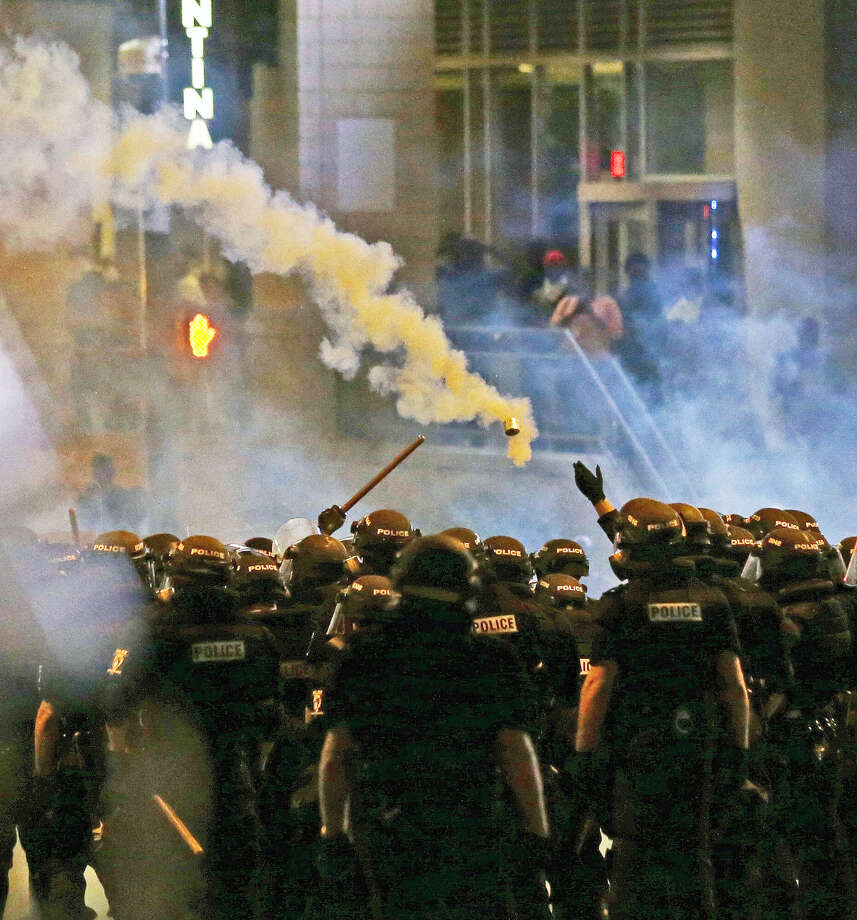Police fire tear gas as protestors converge downtown following Tuesday's police shooting of Keith Lamont Scott in Charlotte, N.C., Wednesday, Sept. 21, 2016. Protesters have rushed police in riot gear at a downtown Charlotte hotel and officers have fired tear gas to disperse the crowd. At least one person was injured in the confrontation, though it wasn't immediately clear how. Firefighters rushed in to pull the man to a waiting ambulance.(AP Photo/Gerry Broome) Photo: AP / Copyright 2016 The Associated Press. All rights reserved.