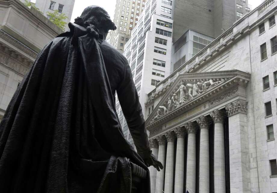 In this Oct. 2, 2014 photo, a statue of George Washington on the steps of Federal Hall faces the facade of the New York Stock Exchange. Photo: AP Photo/Richard Drew, File  / AP