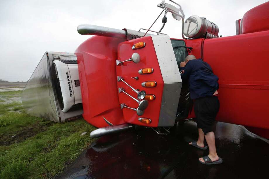Dave McGrew looks into the cabin of an  18-wheeler that was flipped on its side on Highway 59 West as Hurricane Harvey hit the Central Gulf Coast Saturday, Aug. 26, 2017, in Texas. Mcgrew stopped while on his way to check on his family in Victoria, Texas. Photo: Godofredo A. Vasquez, Houston Chronicle / Houston Chronicle