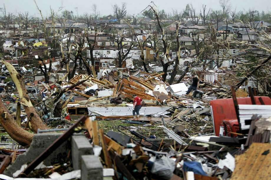 In this May 23, 2011, file photo, Meghan Miller stands in the middle of a destroyed neighborhood as she checks on her sister-in-law's home in Joplin , Mo. A sky-darkening storm was working its way into southwest Missouri around dinnertime on a Sunday evening of May 22, 2011, zeroing in on the city of Joplin. Forecasters knew the storm's potential was fierce and gave early warnings. Then, as storm sirens blared, one of the nation's deadliest tornados hit -- leveling a miles-wide swath of Joplin and leaving 161 people dead. Photo: AP Photo/Jeff Roberson, File   / Copyright 2016 The Associated Press. All rights reserved. This material may not be published, broadcast, rewritten or redistribu