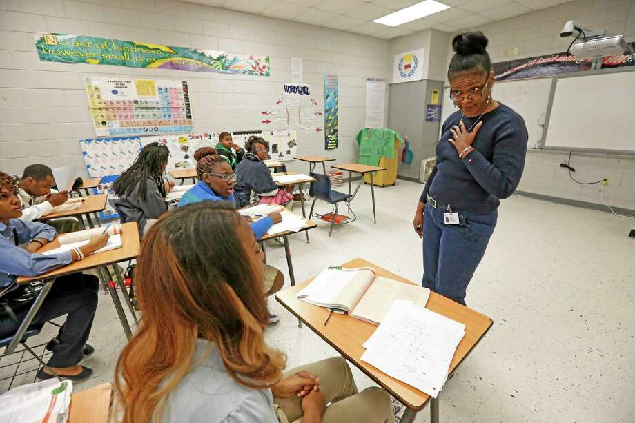 Clarksdale High School chemistry instructor Victoria Dawson, right, encourages her class to solve their equations at the board in Clarksdale, Miss. Photo: AP File Photo  / AP