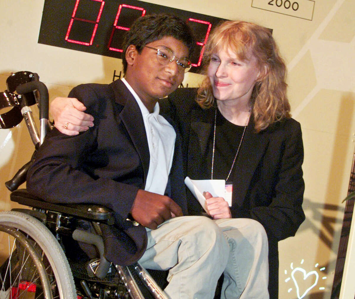 In this Sept. 27, 2000 file photo, actress Mia Farrow poses with her adopted son Thaddeus as they participate in the global summit on polio eradication at United Nations headquarters. Thaddeus Wilk Farrow, died, Wednesday, Sept 21, 2016, after being found seriously injured in his vehicle in Connecticut. The actress adopted Thaddeus, who contracted polio in an orphanage in Kolkata, India, and was paralyzed from the waist down. He was 27.