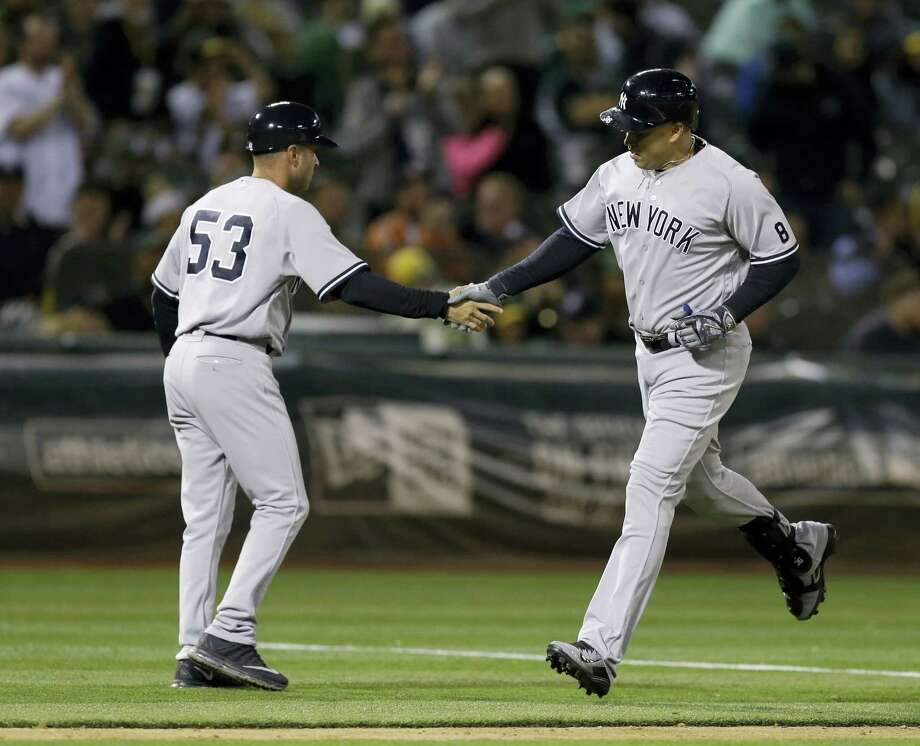 New York Yankees' Carlos Beltran, right, is congratulated by third base coach Joe Espada after hitting a two-run home run off Oakland Athletics' Fernando Rodriguez during the ninth inning of a baseball game Thursday, May 19, 2016, in Oakland, Calif. (AP Photo/Ben Margot) Photo: AP / Copyright 2016 The Associated Press. All rights reserved. This material may not be published, broadcast, rewritten or redistribu