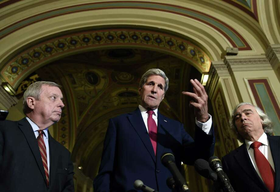 Secretary of State John Kerry, center, flanked by Sen. Richard Durbin, D-Ill., left, and Energy Secretary Ernest Moniz, right, speaks to reporters following their meeting on Capitol Hill in Washington Wednesday on the Iran Nuclear Deal. Photo: AP Photo  / AP