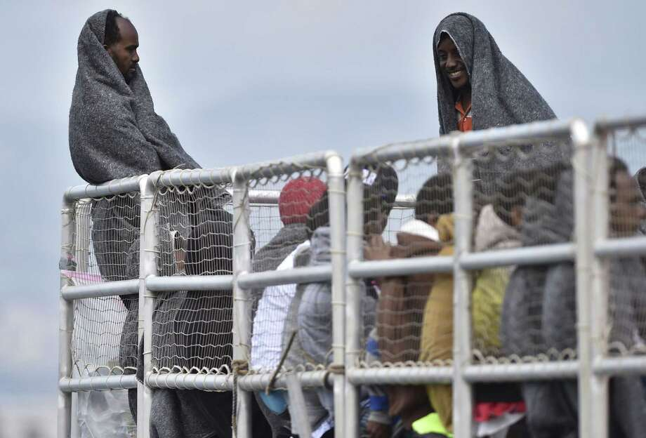 """Migrants wait to disembark from the Migrant Offshore Aid Station (MOAS) vessel """"Phoenix"""" in the harbor of Messina, Sicily, Southern Italy on May 15, 2015. Over 400 migrants, half of them women and children, disembarked in Messina Saturday. Photo: AP Photo/Carmelo Imbesi  / AP"""