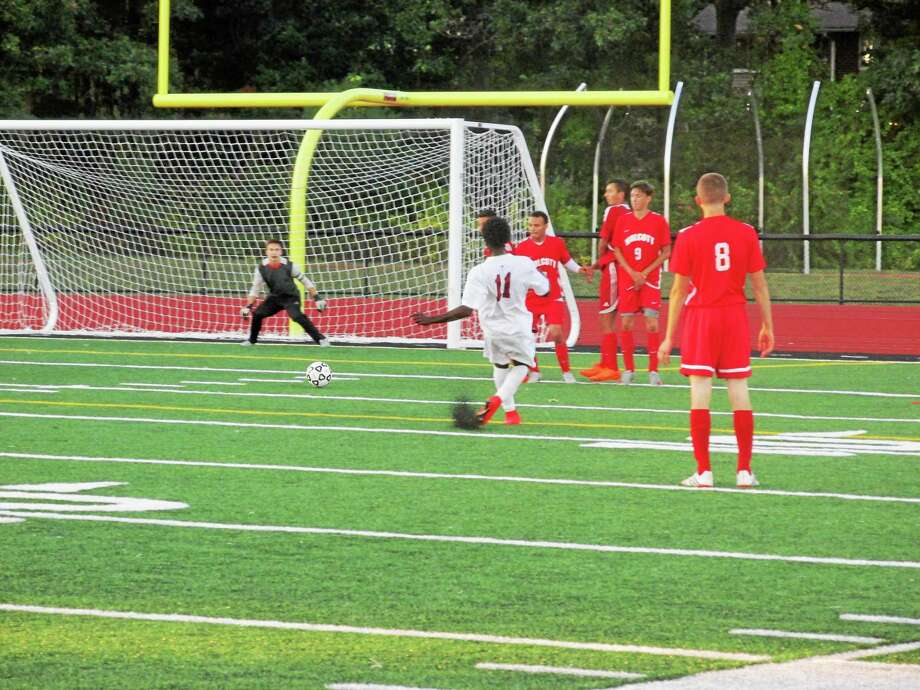 Naseem Thompson sends a direct kick in for Torrington's first goal as Wolcott goalkeeper Nick Roth stands guard. Photo: Peter Wallace — Register Citizen