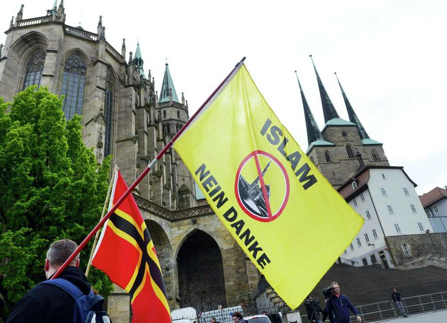 """A demonstrator carries a flag reading """"Islam, no thanks"""" during a rally of nationalist Alternative for Germany against the planned building of a mosque in Erfurt, eastern Germany, Wednesday, May 18, 2016. Photo: AP Photo/Jens Meyer   / AP"""