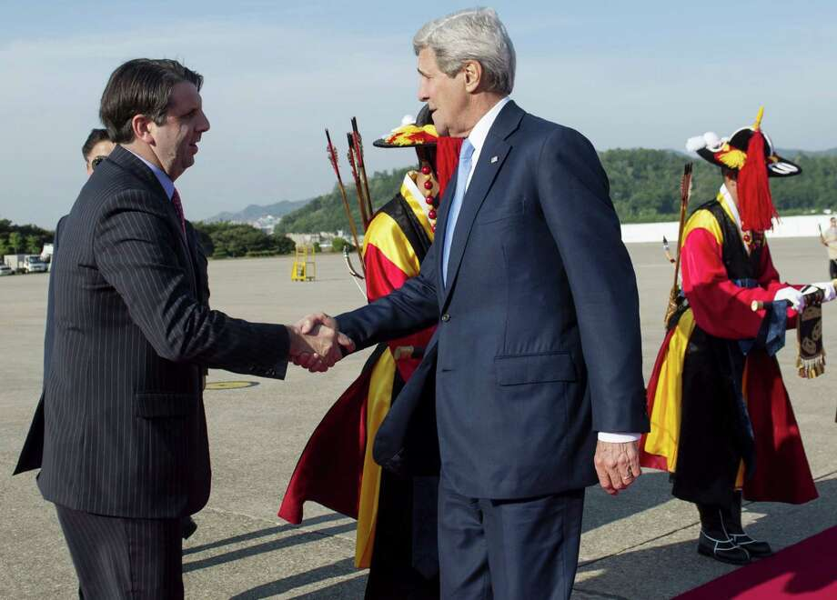 U.S. Secretary of State John Kerry, right, is greeted by U.S. Ambassador to South Korea Mark Lippert upon his arrival at the Seoul Military Airport in Seongnam, South Korea on May 17, 2015. Photo: Saul Loeb/Pool Photo Via AP  / AFP POOL