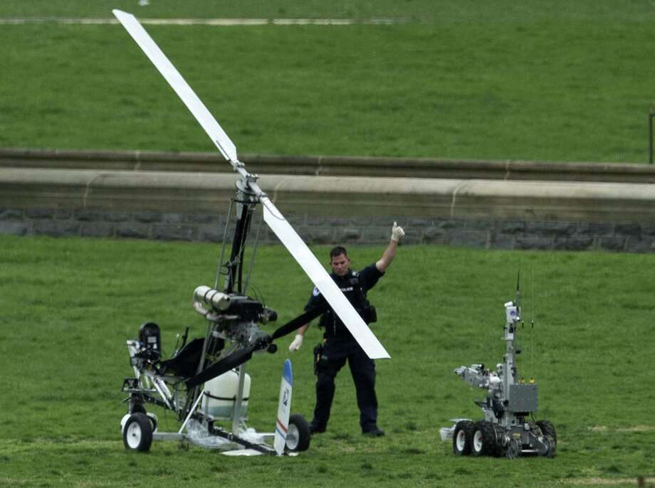 A Capitol Police officer flashes a thumbs up after inspecting the small helicopter a man landed on the West Lawn of the Capitol in Washington on April 15. Police arrested a man who steered his tiny, one-person helicopter onto the West Lawn of the U.S. Capitol Wednesday. Photo: AP Photo  / AP