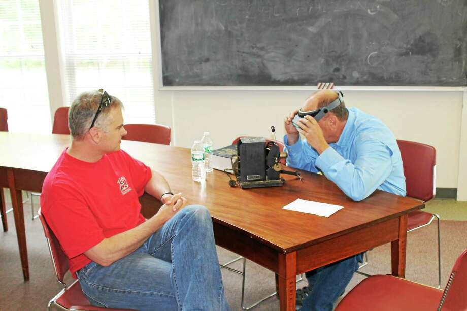 Dave Christensen brought in a rare projector from the early 1900s to the antiques appraisal event in Harwinton on Saturday. Auctioneer and appraiser Michael Tomasiewicz takes a look. Photo: John Nestor — Special To The Register Citizen