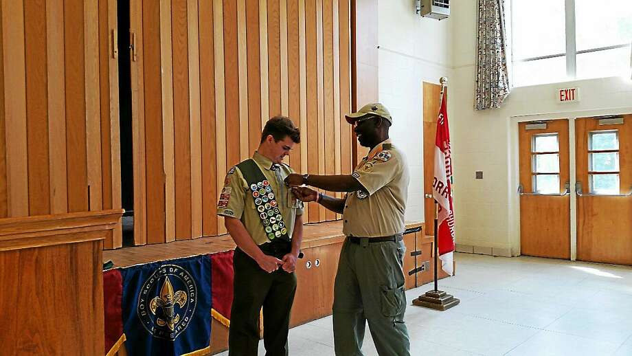 """N.F. Ambery photo Troop 4 Scoutmaster Wilbert """"Wibo"""" Boles, Jr., 65, presents Taylor Yurgalevicz, 18, of Torrington, with service medals. Photo: Journal Register Co."""