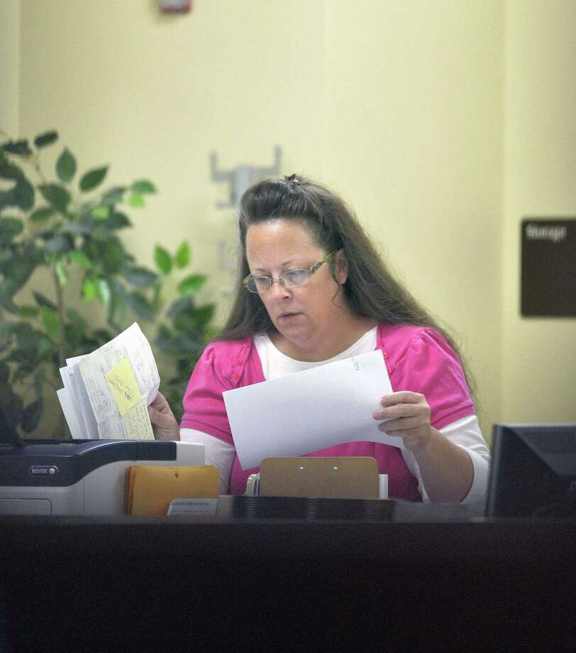 Rowan County Clerk Kim Davis performs her job at the Rowan County Courthouse in Morehead, Ky. on Aug. 18, 2015. Davis is back at work and still not issuing marriage licenses while her case is under appeal. U.S. District Judge David Bunning denied Rowan County Clerk Kim Davis' request to delay his ruling from last week ordering her to issue marriage licenses to gay and lesbian couples. Photo: AP Photo/Timothy D. Easley  / FR43398 AP