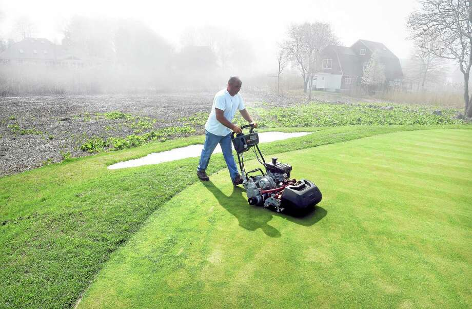 Assistant course supervisor Trevor Hill mows the elevated green on the second hole at Madison Country Club. In the background is marsh that formerly inundated the green with salt water. Photo: Arnold Gold — Register