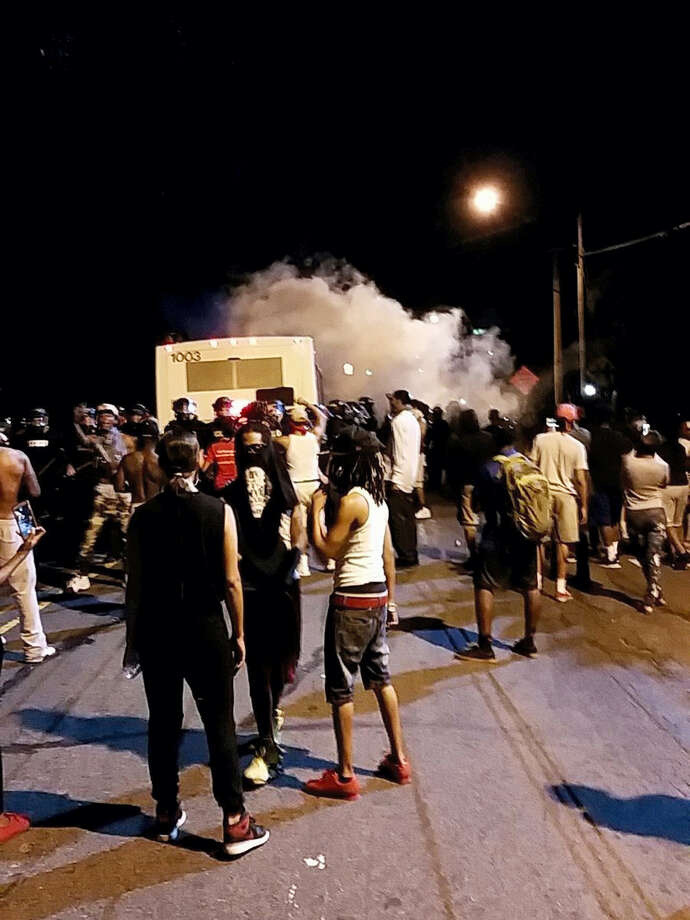 Police fire tear gas into the crowd of protesters on Old Concord Road late Tuesday night, Sept. 20, 2016, in Charlotte, N.C. A black police officer shot an armed black man at an apartment complex Tuesday, authorities said, prompting angry street protests late into the night. The Charlotte-Mecklenburg Police Department tweeted that demonstrators were destroying marked police vehicles and that approximately 12 officers had been injured, including one who was hit in the face with a rock.  (Ely Portillo/The Charlotte Observer via AP) Photo: AP / The Charlotte Observer