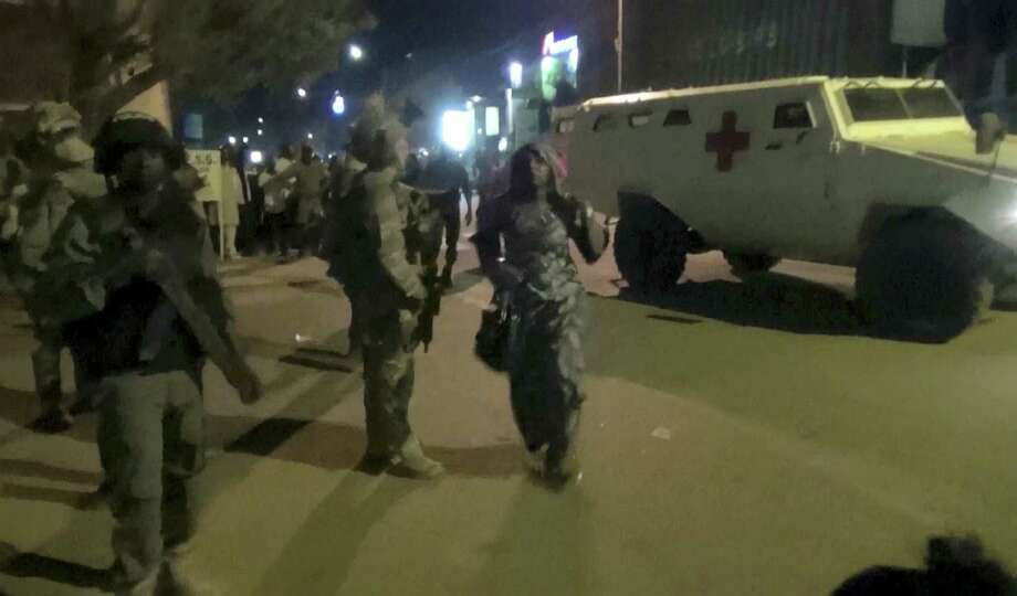 In this image taken from video from AP Television, a freed woman, center, walks past French special forces near the Splendid Hotel, early Saturday, Jan. 16, 2016, in Ouagadougou, Burkina Faso. Heavy gunfire erupted early Saturday as forces from Burkina Faso and France worked to overtake the luxury hotel that had been seized by al-Qaida militants the night before. Photo: AP Television Via AP   / AP Television