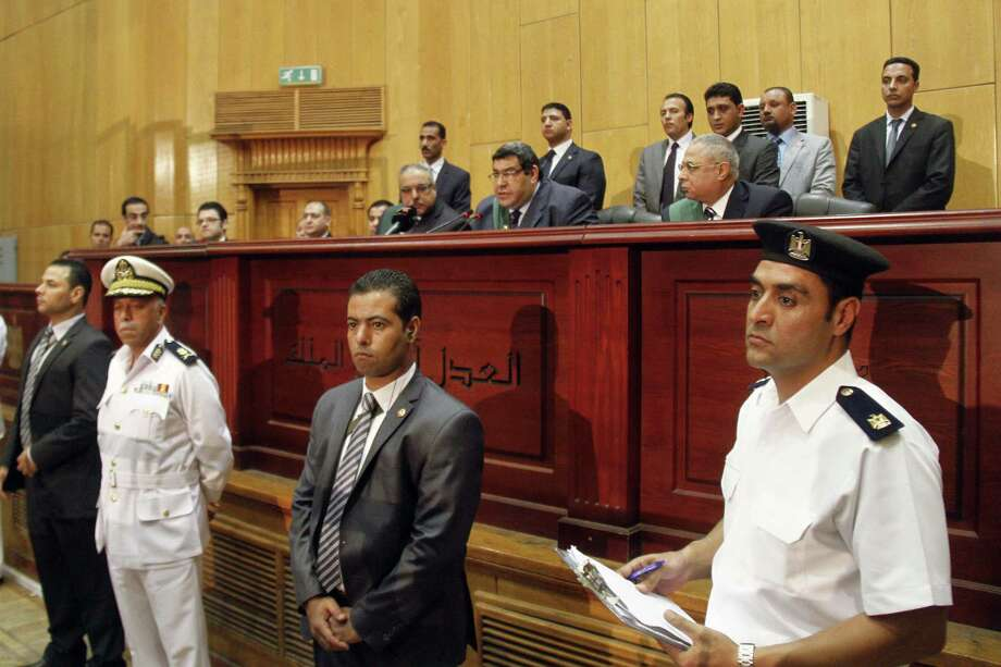 Egyptian Judge Shaaban el-Shami, center, sentences ousted Egyptian President Mohammed Morsi to death over his part in a mass prison break that took place during the 2011 uprising that toppled Hosni Mubarak, in a converted lecture hall in the national police academy in an eastern Cairo suburb, Egypt, Saturday, May 16, 2015. An Egyptian court on Saturday sentenced  Morsi and over 100 others to death including the Brotherhood's spiritual leader, Mohammed Badie, as well as one of the Arab world's best known Islamic scholars, the Qatar-based Youssef al-Qaradawi. (AP Photo/Ravy Shaker, El Shorouk newspaper)   EGYPT OUT Photo: AP / AP