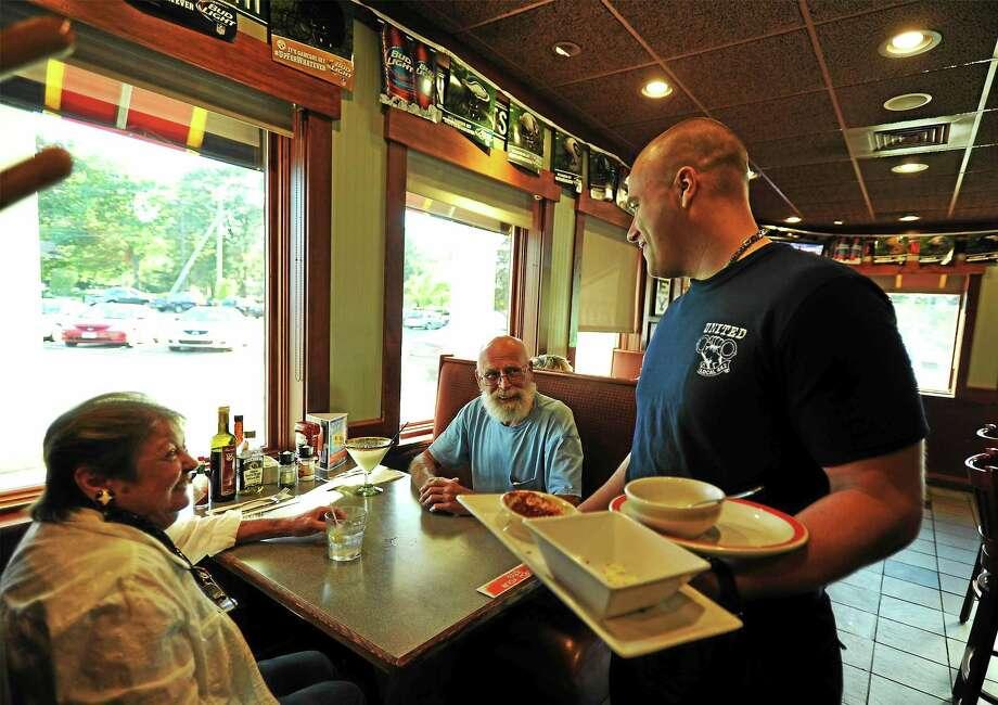 Officer Matt Fifer talks to Jack and Gail Davis of Harwinton at the Tip-A-Cop event. Photo: John Fitts — The Register Citizen