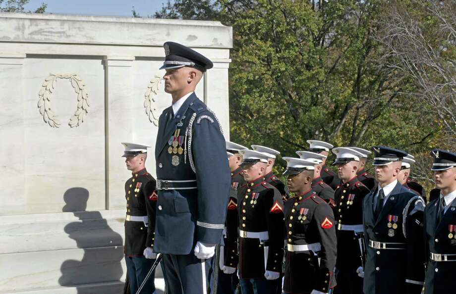 Marine and Air Force honor guards stand beside the Tomb of the Unknowns during a Veterans Day ceremony at Arlington National Cemetery on Nov. 11, 2012. Photo: AP File Photo  / AP