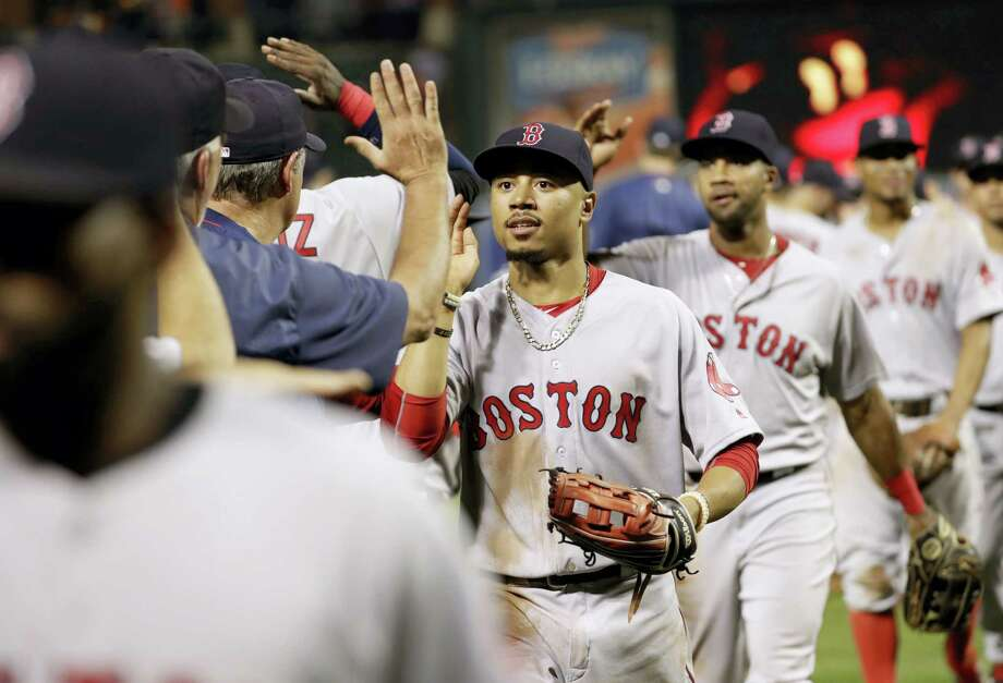 Boston Red Sox right fielder Mookie Betts high-fives teammates after a baseball game against the Baltimore Orioles in Baltimore Tuesday. Boston won 5-2 for its sixth straight victory. Photo: PATRICK SEMANSKY — THE ASSOCIATED PRESS  / Copyright 2016 The Associated Press. All rights reserved.