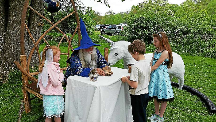 """The Wizard,"" or Bill Dexter, looks into his crystal ball and predicts the good sports fortunes of Tim Shyshkov, 7, of Bethlehem as well as a successful future presidential run for Tim's sister Alina, 9, at the sixth annual Fairy Festival at the Bellamy-Ferriday House & Garde in Bethlehem Saturday. Photo: Noel Ambery — Special To The Register Citizen"