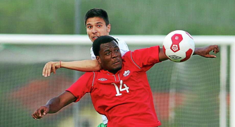 Canada's Cyle Larin, front, challenges for a ball with Ilia Milanov of Bulgaria during a friendly in Ritzing, Austria, on May 23, 2014. Photo: Ronald Zak — The Associated Press File Photo  / AP