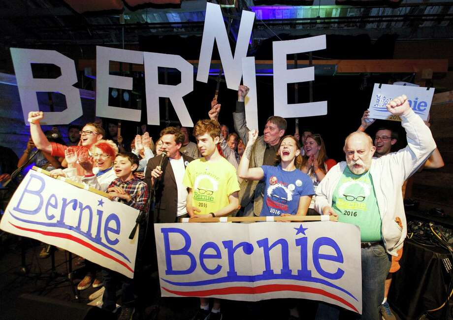 Bernie Sanders supporters react to poll results during the Oregon primary election during a rally in Eugene, Ore., Tuesday. After Sanders won Oregon's Democratic primary this week, two superdelegates announced they'll back the Vermont senator while one declared support for Hillary Clinton. Photo: Ryan Kang — The Register-Guard Via AP  / The Register-Guard