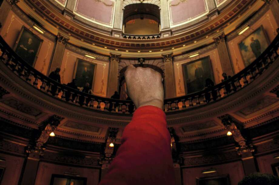 Barbie Biggs raises her fist as more than 150 protestors from Flint and Detroit chant in solidarity in the main lobby asking for the resignation of Gov. Rick Snyder in relation to Flint's water crisis, at the Capitol in Lansing, Mich., Thursday, Jan. 14, 2016. (Sean Proctor/The Flint Journal-MLive.com via AP) MANDATORY CREDIT Photo: AP / The Flint Journal-MLive.com