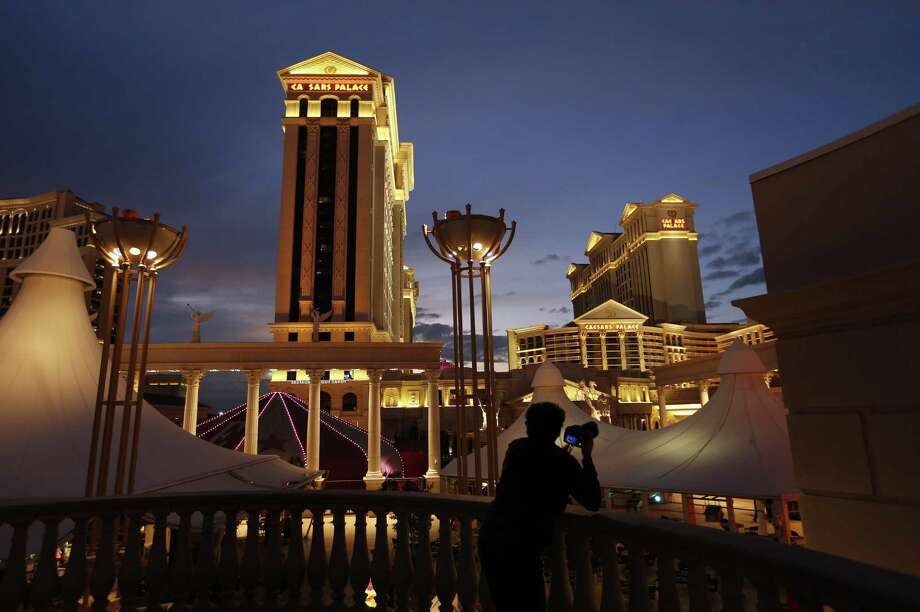 FILE - In this Monday, Jan. 12, 2015 file photo, a man takes pictures of Caesars Palace hotel and casino, in Las Vegas. A cash-strapped division of casino giant Caesars Entertainment Corp. said early Thursday Jan. 15, 2015 that it filed for bankruptcy protection in Chicago, hoping the court agrees to its plan to get out from under $18.4 billion of debt.  (AP Photo/John Locher, File) Photo: AP / AP