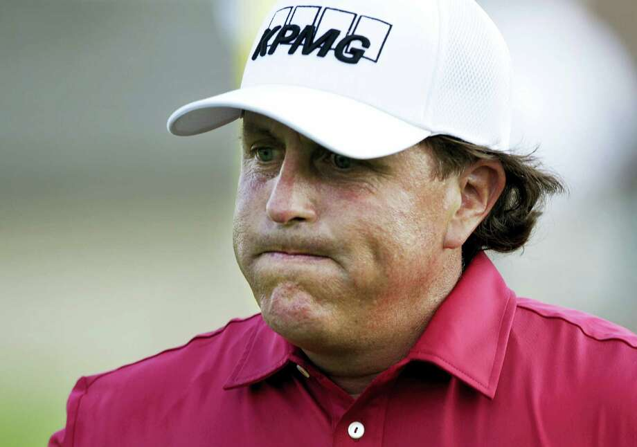 FILE - In this May 29, 2014, file photo, Phil Mickelson reacts after making double bogey on the 17th hole during the first round of the Memorial golf tournament in Dublin, Ohio. The Securities And Exchange Commission is filing a complaint against Mickelson related to insider trading. The SEC says in 2012, high-profile sports bettor Billy Walters called Mickelson, who owed him money, and urged him to trade Dean Foods stock. The SEC says Mickelson did so the next day and made a profit of $931,000.  The SEC says Walters received tips and business information about Dean Foods Co. from former Dean Foods director Thomas Davis between 2008 and 2012.  (AP Photo/Jay LaPrete, File) Photo: AP / FR52593 AP