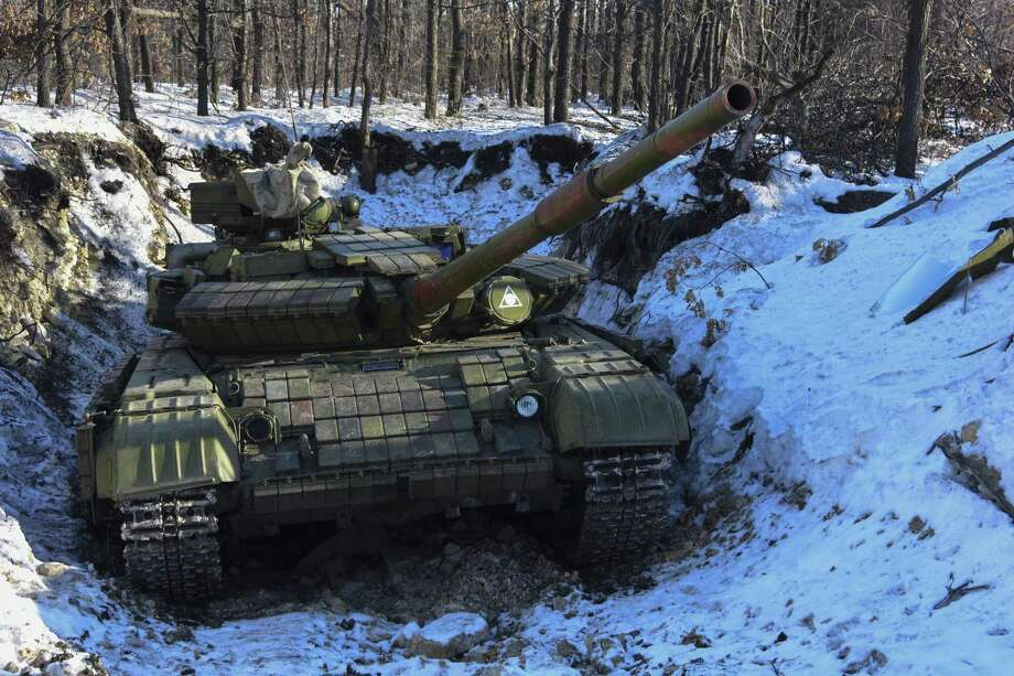 In this Wednesday, Jan. 14, 2015 photo Russian-backed separatist's tank is placed in a fortified position at the check-point north of Luhansk, Eastern Ukraine.  An attack on a passenger bus in eastern Ukraine killed 12 people Tuesday, likely dealing the final blow to hopes that a short-lived and shaky cease-fire could take hold. (AP Photo/ Mstyslav Chernov) Photo: AP / AP