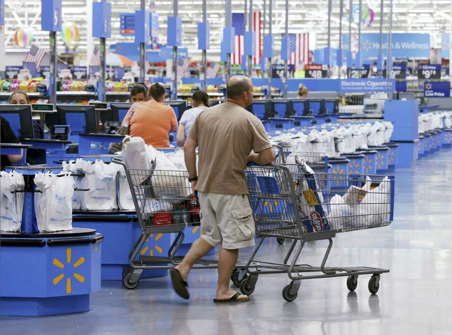 In this Thursday, June 4, 2015, photo, shoppers walk from the checkout at a Wal-Mart Supercenter store in Springdale, Ark. Wal-Mart announced Friday, Jan. 15, 2016, that it is closing 269 stores, more than half of them in the U.S. and another big chunk in its challenging Brazilian market. The store closures will start at the end of January. Photo: AP Photo/Danny Johnston / AP